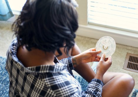 Woman looking at pregnancy wheel in her living room