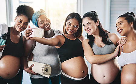 Friends pose for a photo after their prenatal yoga class